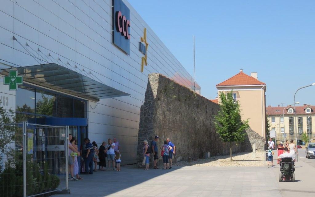 Modernes Einkaufszentrum neben alter Stadtmauer